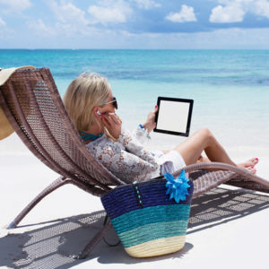 Woman with tablet computer relaxing on beach