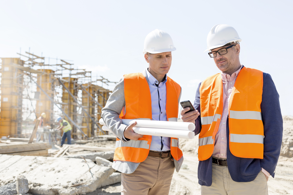 Architect and project manager looking at a mobile phone whilst standing on a construction site