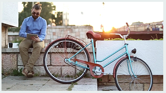 Hipster using tablet with top knot, beard and bike, sunset effect