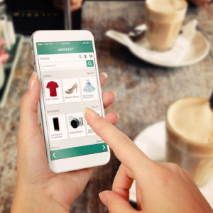 Online shopping on mobile at cafe with coffees